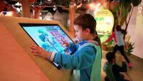 Spel van de jongens beweegt het speelcomputer, Kinderen hun vingers langs het grote aanrakingsscherm, kindspel met modern aanraki stock footage