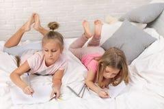 Spel van twee het kleine jonge geitjesmeisjes in de slaapkamer stock foto
