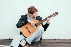 Spela den akustiska gitarren Arkivbild