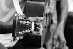 Spela den akustiska gitarren i svartvitt royaltyfria bilder