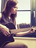 Spela den akustiska gitarren vid fönstret Arkivfoton