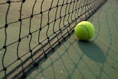 Spela den modiga tennisbollen på tennisbanan Arkivfoton