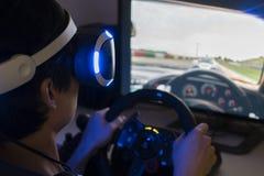 Spela den tävlings- videospelet med VR-hörlurar med mikrofon hemma arkivfoton