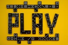 Spela dominobrickor, begrepp Gul bakgrund royaltyfria bilder