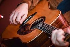 Spela för akustisk gitarr closeupmanhänder som spelar den akustiska gitarren Arkivfoton