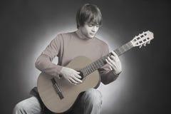 Spela för gitarrist för akustisk gitarr fotografering för bildbyråer