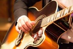 Spela för gitarrist för akustisk gitarr. arkivfoto