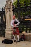 Spela för London UK Förenade kungariket skotskt man som är säckpipe- arkivfoto