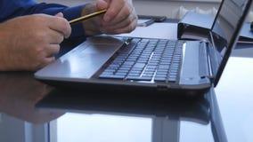 Spela för manhänder som är nervöst med blyertspennan över bärbar datortangentbordet arkivfoto