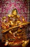 Spela för Saraswati hinduiskt gud som är sittar/vina Arkivbild