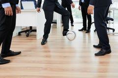 Spela fotboll med kollegor royaltyfri foto