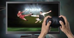 Spela fotbolldataspelen med kontrollanten i händer Arkivbilder