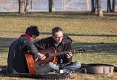 Spela gitarren i en parkera Arkivbild
