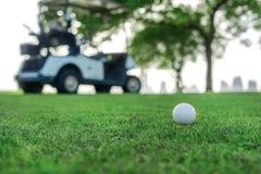 Spela golf och en golfvagn Golfboll är på utslagsplatsen för en golf Arkivfoton