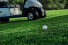 Spela golf och en golfvagn Golfboll är på utslagsplatsen för en golf Arkivbilder