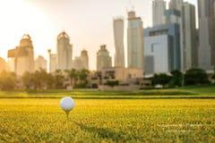 Spela golf på solnedgången Golfboll är på utslagsplatsen för en golfboll Arkivfoto