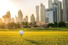 Spela golf på solnedgången Golfboll är på utslagsplatsen för en golfboll Arkivbild