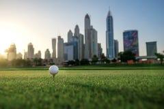 Spela golf på solnedgången Golfboll är på utslagsplatsen för en golfboll Fotografering för Bildbyråer