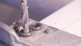 Spela golfboll i hål att borras in i aluminium och metall genom att använda den elektriska drillborren Aluminium- eller metallbor arkivfoton