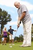 Spela golfboll i hål för hög man arkivbilder