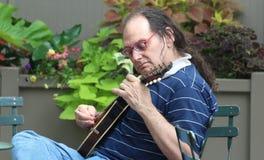 Spela hans ukulele Fotografering för Bildbyråer