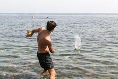 Spela i havet med en sten Arkivbild
