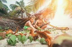 Spela i Robinzones: fadern och sonen byggde en koja från palmträdet arkivbilder