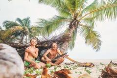 Spela i Robinzones: fadern och sonen byggde en koja från palmträdet royaltyfria bilder