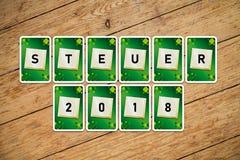 Spela kort med text 'Steuer 2018 'på ett trägolv arkivfoto