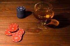 Spela kort och vinexponeringsglas av konjak på den wood tabellen Arkivfoto