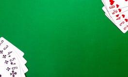 Spela kort på en grön tabell royaltyfria foton