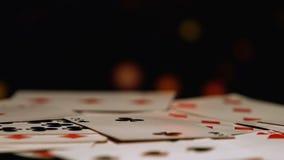 Spela kort som omkring vänder mot mörk bakgrund, dobbleriaffär, kasino arkivfilmer