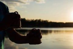 Spela maracas eller caxixi för ett musikinstrument på bakgrundshimmel på solnedgången Arkivfoto