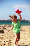 Spela med vatten på den sandiga stranden Royaltyfri Bild