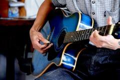 Spela musik på den blåa gitarren arkivbild