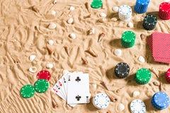 Spela på semesterbegreppet - vit sand med snäckskal, kulöra pokerchiper och kort Top beskådar royaltyfria bilder