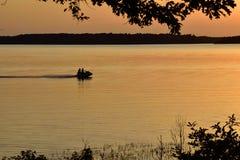 Spela på sjön på den guld- solnedgången till och med trädkontur Arkivfoto