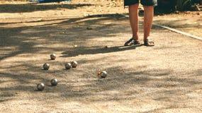 Spela Petanque i parkera - metallbollar och den orange träbollen vaggar på gården med ett mananseende i solen royaltyfri fotografi