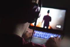 Spela videospel med bärbara datorn Den unga mannen spelar handlingleken fotografering för bildbyråer