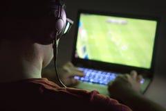 Spela videospel med bärbara datorn Den unga mannen spelar online-fotboll arkivbild