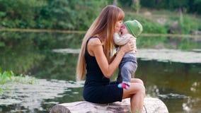 Spelar den övre modern för slutet med hennes son nära vattnet arkivfilmer