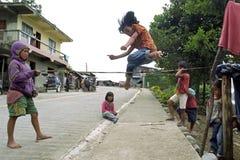 Spelar den filippinska flickan för den höga banhoppningen, en lek Royaltyfri Fotografi