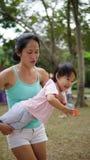 Spelar det bärande lilla barnet för den asiatiska kvinnan i familj utomhus- Arkivfoto