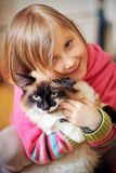 Spelar en flicka och med en katt Royaltyfri Foto