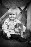 Spelar en flicka och med en katt Arkivfoto
