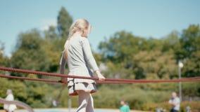 spelar går årig blond flicka 7 på lekplats och på rep i sommar arkivfilmer