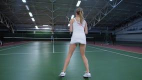 Spelare för yrkesmässig sport som har utbildning på den inomhus domstolen som förbättrar expertis Kvinnan i den vita sportdräkten stock video