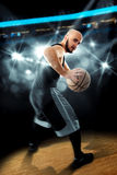 Spelare i basket på golvet med bollen i händer som ser awa Arkivfoto