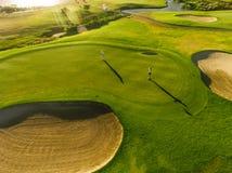Spelare på en grön golfbana arkivbild