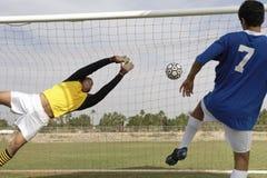 Spelare som gör poäng mål medan målvaktdykning för att spara den Royaltyfri Fotografi